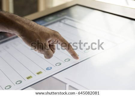 Hand touching touch screen. Asian, brown, hairy hand scrolling through list. Interactive screen #645082081