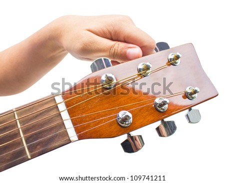 Hand tuning a guitar from headstock isolated on white background.