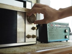 Hand tuning vintage radio with blurred background of antique transistor radio. Once upon a time concept, Nostalgic memories theme. (close up, selective focus, space for text, article layout design)