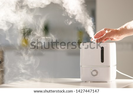 Hand turn on aroma oil diffuser on the table at home, steam from the air humidifier, free space. Ultrasonic technology, increase in air humidity indoors, comfortable living conditions, moisture.