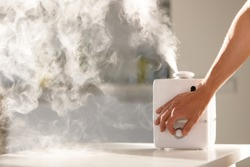 Hand turn on aroma oil diffuser on the table at home, steam from the air humidifier. Ultrasonic technology, increase in air humidity indoors, comfortable living conditions.
