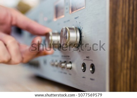 Hand turning a dial on a vintage home stereo equipment