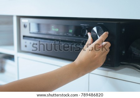 Hand turning on Home-theater amplifier system