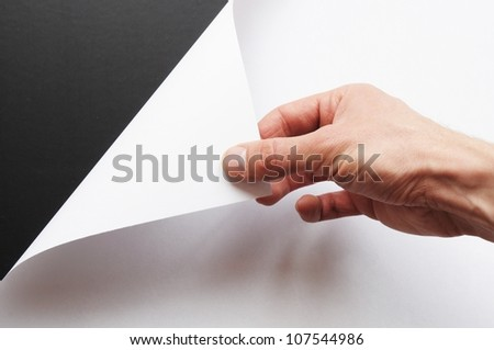hand turning over blank sheet of paper
