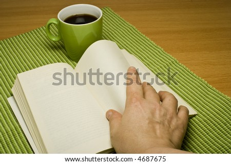 Hand turning pages in a book on a table with a green coffee cup. The book has blank pages.