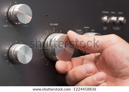 Hand turning up the volume in a stereo #1224458836