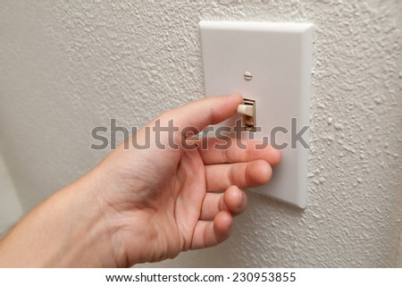 Hand turning wall light switch off