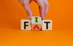 Hand turns a cube and changes the word fat to fit. Beautiful orange background. Lifestyle and healthy concept. Copy space.
