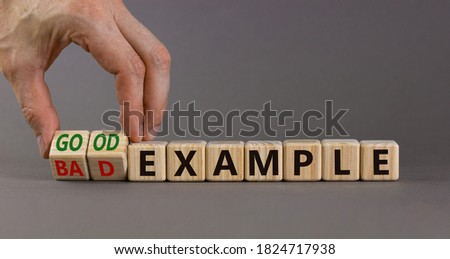 Hand turns a cubes and changes the expression 'bad example' to 'good example'. Beautiful grey background. Business concept. Copy space. ストックフォト ©