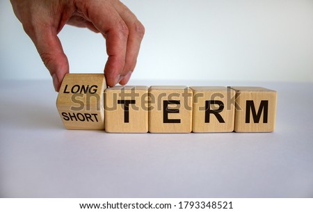 Hand turns a cubes and changes the expression 'SHORT TERM' to 'LONG TERM' or vice versa. Beautiful white background. Business concept, copy space. Stockfoto ©