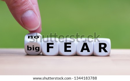 "Hand turns a dice and changes the expression ""big fear"" to ""no fear"". #1344183788"