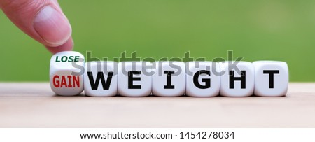"""Hand turns a dice and changes the expression """"gain weight"""" to """"lose weight""""."""