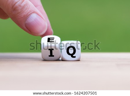 "Hand turns a dice and changes the expression ""IQ"" (Intelligence Quotient) to ""EQ"" (Emotional Intelligence/Quotient)."