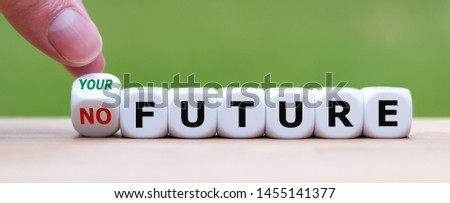"""Hand turns a dice and changes the expression """"no future"""" to """"your future""""."""