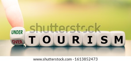 """Hand turns a dice and changes the expression """"over tourism"""" to """"under tourism""""."""