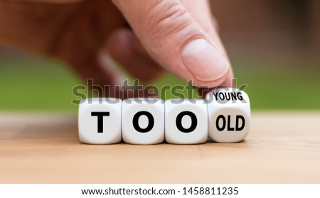 "Hand turns a dice and changes the expression ""too old"" to ""too young"" , or vice versa. #1458811235"