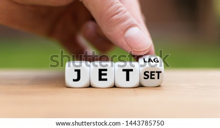 "Hand turns a dice and changes the word ""jet-set"" to ""jet-lag"". #1443785750"
