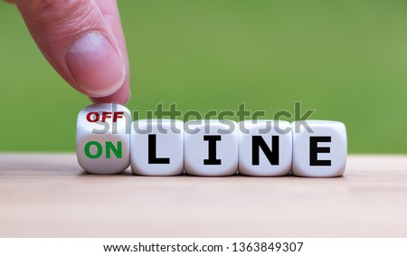 Hand turns a dice and changes the word 'offline' to 'online' (or vice versa). Foto stock ©