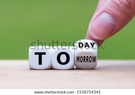 Hand turns a dice and changes the word 'tomorrow' to 'today', or vice versa. Сток-фото ©