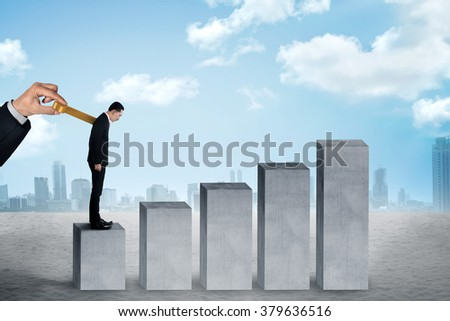 Hand turns clockwork on the back of business person, concept to control work #379636516