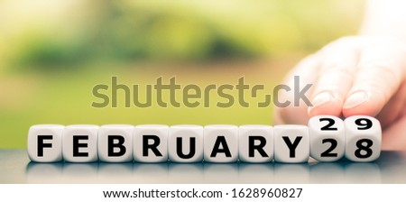 "Photo of  Hand turns dice and changes the date from ""February 28"" to ""February 29""."