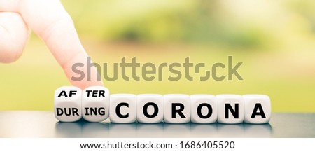 """Hand turns dice and changes the expression """"during Corona"""" to """"after Corona""""."""