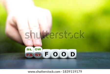 """Photo of  Hand turns dice and changes the expression """"fast food"""" to """"slow food""""."""