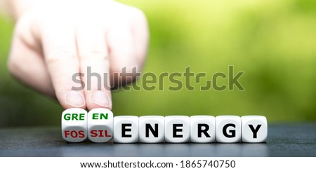 Hand turns dice and changes the expression 'fossil energy' to 'green energy'. ストックフォト ©