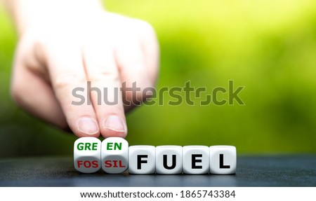 Hand turns dice and changes the expression 'fossil fuel' to 'green fuel'. ストックフォト ©