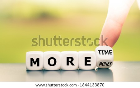 "Photo of  Hand turns dice and changes the expression ""more money"" to ""more time""."