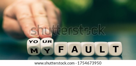 Hand turns dice and changes the expression 'my fault' to 'your fault'. Сток-фото ©