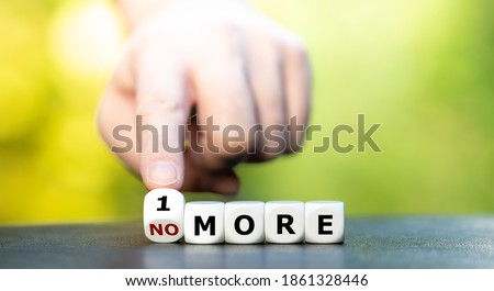 "Photo of  Hand turns dice and changes the expression ""no more"" to ""1 more""."