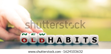 Hand turns dice and changes the expression 'old habits' to 'new habits'. Stockfoto ©