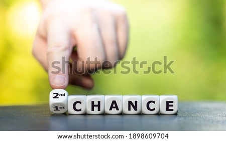 Hand turns dice and changes the expression '1st chance' to '2nd chance'. Stock fotó ©