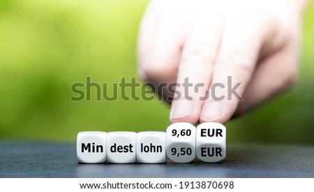 Hand turns dice and changes the German expression 'Mindestlohn (minimum wage) 9.50 EUR' to 'Mindestlohn (minimum wage) 9.60 EUR'. Stock photo ©