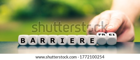 Hand turns dice and changes the German word 'Barriere' (barrier) to 'Barrierefre' (barrier free). ストックフォト ©