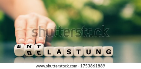 Hand turns dice and changes the German word 'Belastung' ('work load') to 'Entlastung' ('relief'). Stock photo ©