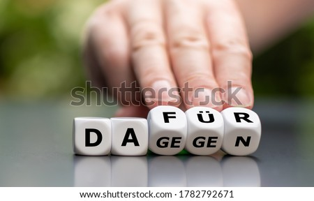 Hand turns dice and changes the German word 'dagegen' (cons) to 'dafuer' (pros) Foto stock ©