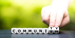 Hand turns dice and changes the word communism to community.