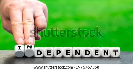 Hand turns dice and changes the word 'dependent' to 'independent'. Сток-фото ©