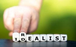Hand turns dice and changes the word idealist to realist.