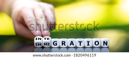 Hand turns dice and changes the word 'immigration' to 'integration'. Foto stock ©