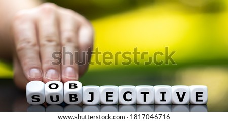 Hand turns dice and changes the word 'subjective' to 'objective'. Foto stock ©