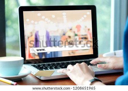 Hand tying labtop computer with www. on search bar over blur store background on screen, on line shopping ,business, E-commerce, technology and digital marketing concept background #1208651965