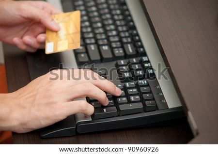 hand typing credit card number for online shopping