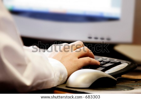 Hand typing on computer keyboard with mouse and monitor- represents computer work at office/school/home, and/or surfing the internet.