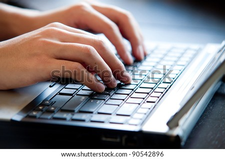 hand typing on laptop keyboard