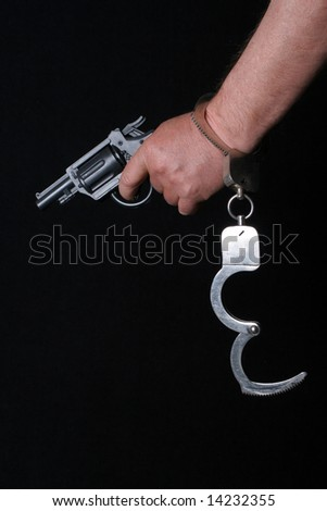 Hand use gun and wearing handcuffs - stock photo