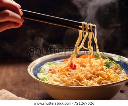 Hand uses chopsticks to pickup tasty noodles with smokes.