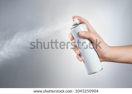 Hand using a spray on white background